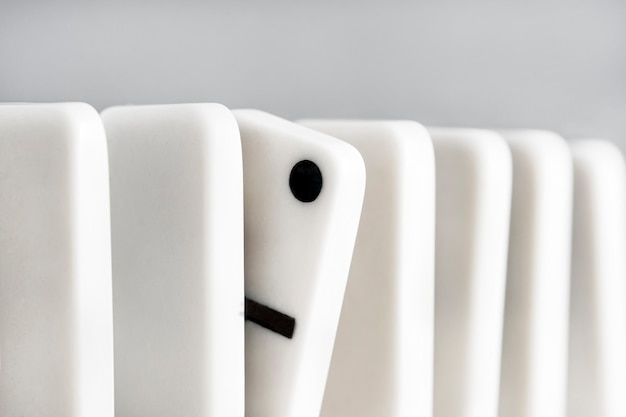 Concept of non-standard thinking in business. row of white dominoes on a light background.