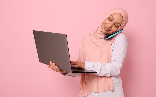 바쁜 아랍 이슬람 비즈니스 여성, 히잡을 쓴 프리랜서, 동시에 노트북 작업을 하는 동안 휴대 전화로 이야기하는 개념. 복사 공간이 분홍색 배경에 격리되었습니다. 자신감 있는 초상화