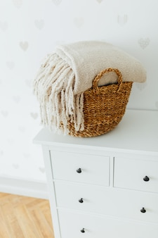 Concept of a cozy interior and housewarming - big basket with clean linen on the dresser