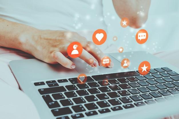 ソーシャルメディアでラップトップを使用して、いいね、コメント、フォロワーを獲得する人の概念。