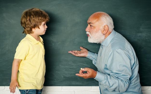 Понятие пенсионного возраста. учитель начальной школы и ученик в классе. молодой мальчик делает свое