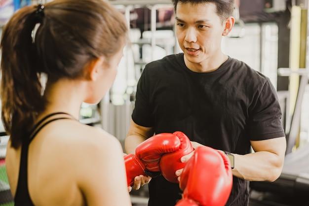 スポーツコーチ、男性のアジアのコーチ、ボクシングに女性のアマチュアボクサーを教えることの概念。