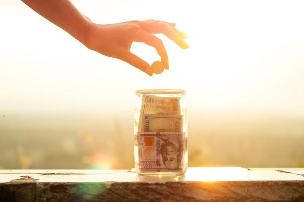Концепция накопления денег в стеклянной банке на солнечном свете с помощью солнца