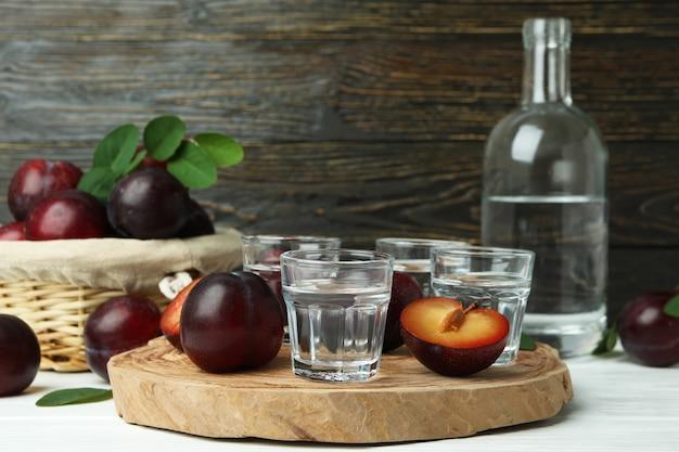 나무 배경에 매실 보드카와 알코올의 개념