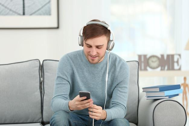 オーディオブックのコンセプト。自宅のソファに座っているヘッドフォンと電話を持つハンサムな若い男