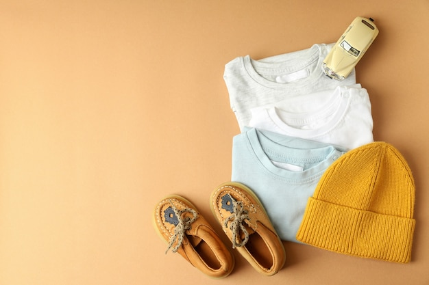 Концепция детской одежды на бежевом фоне.