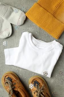 Концепция детской одежды на сером текстурированном фоне.