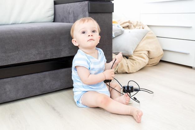 위험에 처한 아기의 개념입니다. 혼자 바닥에 앉아 전기 케이블을 가지고 노는 귀여운 아기