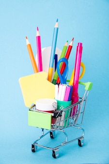 学校に戻るの概念。学用品付きのショッピングカート。