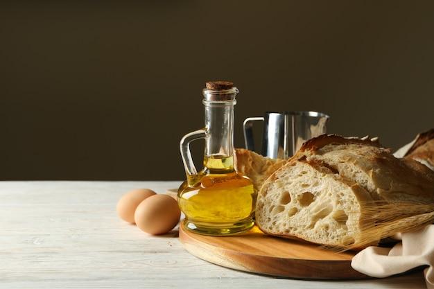 白い木製の背景に焼きたてのパンとベーカリー製品の概念