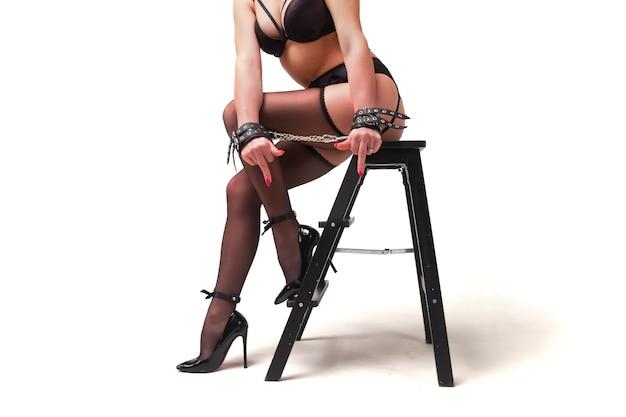 Концепция игр бдсм. сексуальная брюнетка с идеальной фигурой в черном нижнем белье фетиш и маска кошки в наручниках позирует на белом изолированном фоне. сексуальная игрушка для девочек со связанными руками. копировать пространство