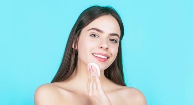 美容、健康治療の概念。美容とスパ。化粧用スポンジを使用。スポンジを使用して肖像画の女性。コットンパッドのスキンケアコンセプトを使用して、清潔で完璧な新鮮な肌を持つ美しいブルネットの女性。