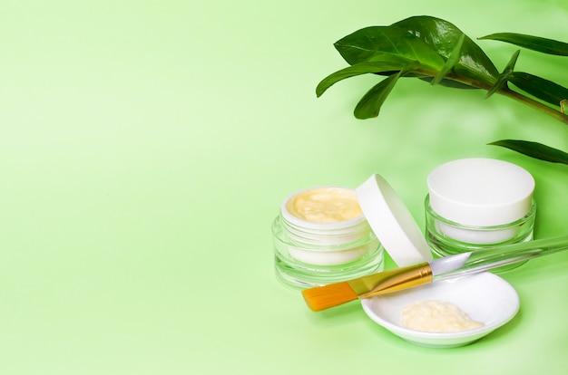 Понятие красоты. натуральная косметика класса люкс, крем, маска для ухода за кожей. аксессуары косметолога на зеленом фоне, копией пространства