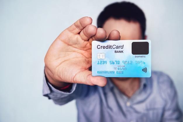 Концепция биометрической проверки кредитной карты. держатель карты показывает платежную карту с датчиком пальца. совершите покупку с помощью сканера отпечатков пальцев. молодой человек с кредитной картой нового поколения.