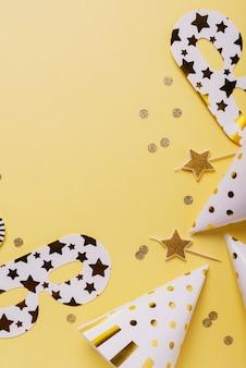 黄色の背景にパーティーハット、マスク、キャンドルで誕生日パーティーのコンセプト。