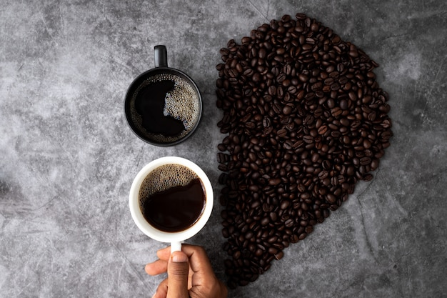 ブラックコーヒーの恋人の概念、手は一杯のコーヒーを保持、上記のテーブルからの眺め。