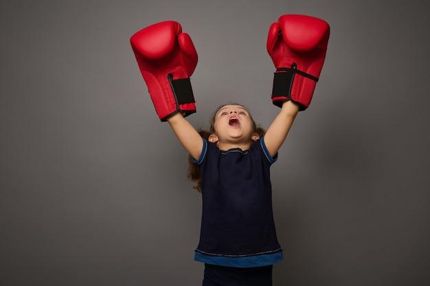 コピースペースのある灰色の背景の価格への打撃の概念。小さな子供、赤いボクシンググローブを身に着けている愛らしい女の子のボクサーは、勝者の位置で手を上げます。ボクシングデーとブラックフライデーの撮影