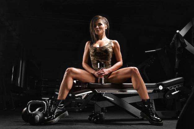 ボディービルのコンセプト、美しいボディの構造、ジム。スポーツ少女は腕二頭筋の練習をします