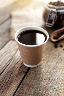 ブラックコーヒーエスプレッソの紙コップ、ガラスの瓶にドライローストコーヒー豆、古い木製のテーブルでスプーンでカフェでの朝食のコンセプト