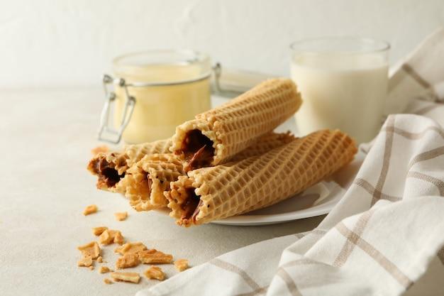 Концепция завтрака с вафельными трубочками со сгущенным молоком на белой текстуре