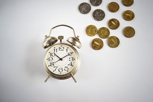 비즈니스의 개념은 시간과 돈입니다. 알람 시계 1 개와 동전