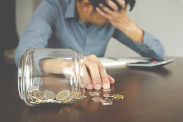 비즈니스 손실의 개념입니다. 돈 절약이 깨졌습니다. bussisnessman은 자신의 돈을 관리할 수 없기 때문에 절망적이며 우울합니다.