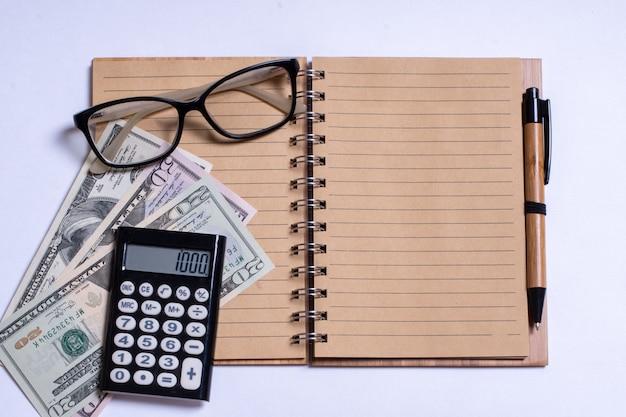 ビジネスの概念、上面図、電卓、ペン、メガネ、白い背景の上のノート。白い背景の上の個人所得税、電卓、現金、メモ帳。コピースペース