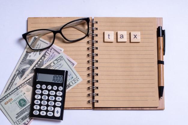 ビジネスの概念、上面図、電卓、ペン、メガネ、白い背景に税金で書かれたノートブック。白い背景の上の個人所得税、電卓、現金、メモ帳。コピースペース