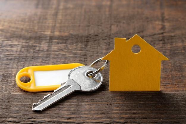 Концепция покупки дома. ключи с брелком и домом на коричневом деревянном фоне.