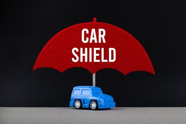 自動車保険の概念。テキストカーシールド付きの赤い傘の下の青い車。