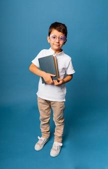 子供の頃、学校、教育、人々の概念-本を持っている眼鏡をかけた幸せな笑顔の少年。
