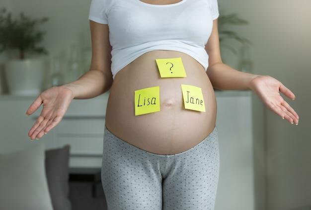 Концепция выбора имени ребенка. молодая царствующая женщина с именами, написанными на животе