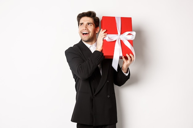クリスマス休暇、お祝い、ライフスタイルの概念。新年を楽しんでいる興奮した男の画像、白い背景に立って、中身を推測するためにギフトボックスを振る。