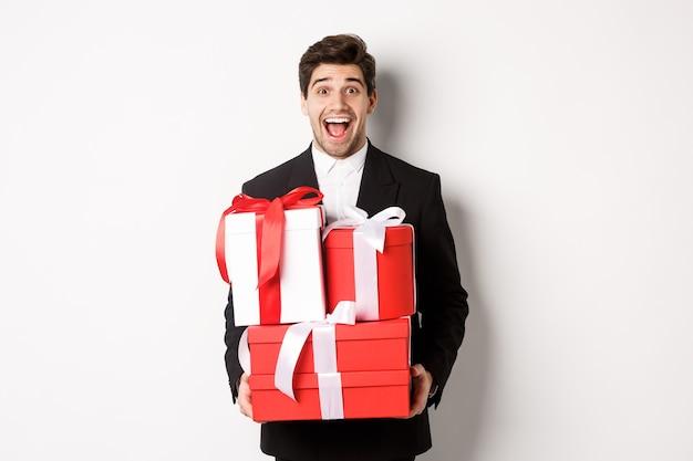 Концепция рождественских праздников, празднования и образа жизни. изображение красивого изумленного парня в костюме, держащего новогодние подарки и улыбающегося, стоящего на белом фоне