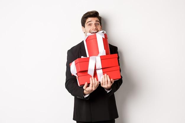 クリスマス休暇、お祝い、ライフスタイルの概念。スーツを着た幸せな男の画像は、新年のプレゼントを運び、贈り物と笑顔で箱を持って、白い背景に立って