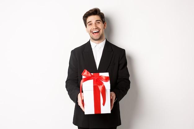クリスマス休暇、お祝い、ライフスタイルの概念。黒のスーツを着て、クリスマスプレゼントを持って、笑顔で、白い背景に立ってうれしそうなハンサムな男。