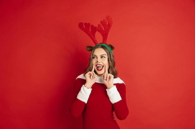 クリスマス、正月、冬の気分、休日のコンセプト。ギフト用の箱を引くサンタのトナカイのような長い髪の美しい白人女性。