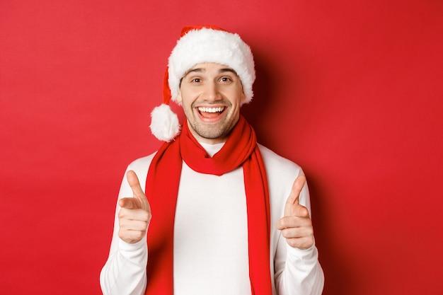 クリスマス、冬休み、お祝いのコンセプトです。サンタの帽子とスカーフで生意気な男、笑顔でカメラに指を指して、新年あけましておめでとうございます、赤い背景の上に立って