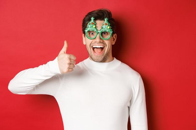 クリスマス、冬休み、お祝いのコンセプトです。パーティーグラスで興奮したハンサムな男、面白がって笑って、親指を立てて、赤い背景の上に立っています。