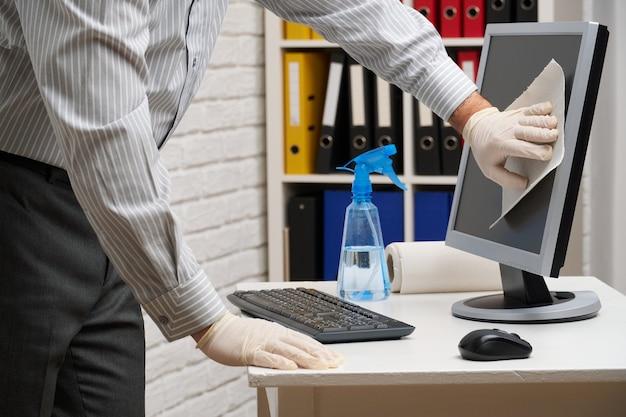 オフィスの掃除または消毒の概念-ビジネスマンは職場、コンピューター、机を掃除し、スプレーガンと紙ナプキンを使用します。微生物、ウイルス、汚れから表面をきれいにします。
