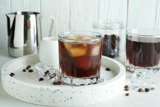 白い織り目加工のテーブルでアイスコーヒーを調理する概念