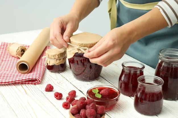 白い木製のテーブルでラズベリージャムを調理するの概念。