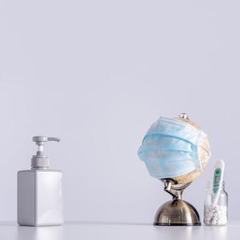 Концепция пандемии коронавируса covid-19 в мире. глобус с маской для лица, дезинфицирующим средством, лекарством, изолированным клиническим термометром
