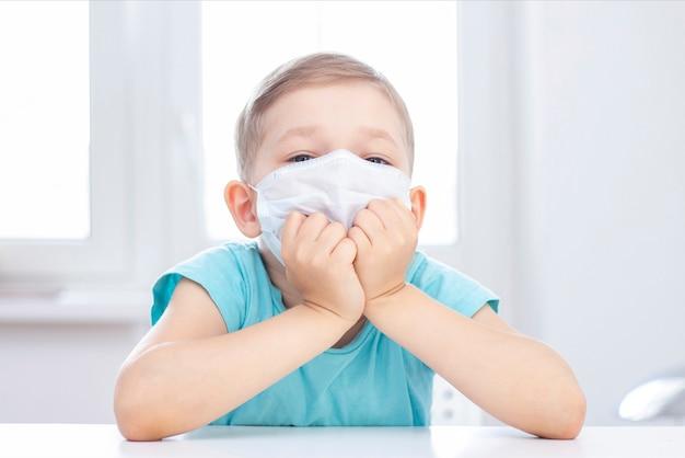 コロナウイルス感染の概念。マスクの少年は室内の椅子に座っています。退屈で悲しい少年