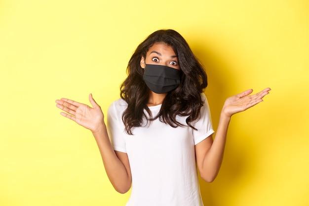 코로나바이러스, 전염병 및 생활 방식의 개념. 얼굴 마스크를 쓴 귀여운 아프리카계 미국인 소녀의 이미지, 어깨를 으쓱하고 아무 것도 모르고 노란색 배경 위에 서 있습니다.