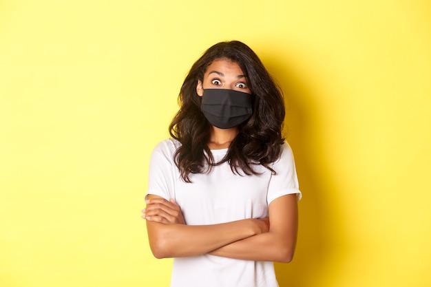 코로나바이러스, 전염병 및 생활 방식의 개념. 노란색 배경 위에 서서 멋진 것을 보고 놀란 아프리카계 미국인 소녀의 얼굴 마스크 이미지.