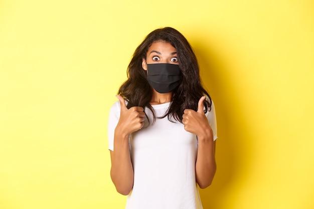 코로나바이러스, 전염병 및 생활 방식의 개념. 검은색 얼굴 마스크를 쓴 아름다운 아프리카계 미국인 소녀의 초상화, 엄지손가락을 치켜들고 놀란 표정을 하고 노란색 배경을 추천합니다.