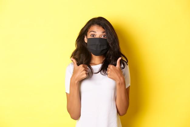 코로나바이러스, 전염병 및 생활 방식의 개념. 검은색 얼굴 마스크를 쓴 아름다운 아프리카계 미국인 소녀의 초상화, 좋은 노란색 배경처럼 승인을 위해 엄지손가락을 위로 올려보입니다.