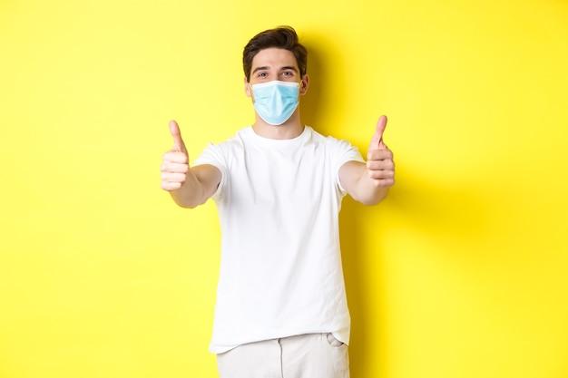 코로나바이러스, 전염병 및 사회적 거리의 개념. 의료 마스크로 covid-19로부터 자신을 보호하는 자신감 있는 남자, 승인에 엄지손가락을 보여주는 노란색 배경