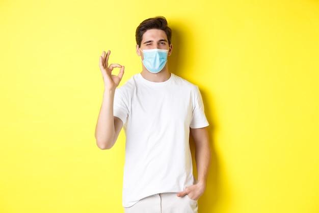 コロナウイルスの概念、パンデミックおよび社会的距離。大丈夫な兆候とまばたき、黄色の背景を示す医療マスクの自信を持って若い男。